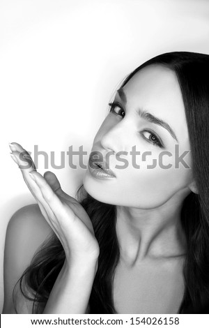 Blowing a kiss. Black and white image of beautiful young women blowing a kiss and looking at camera