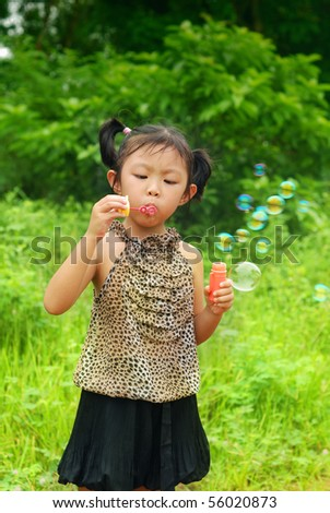 Blowing bubbles in the park for children - stock photo