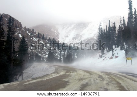 Blowing snow covers road during windy day on Pike's Peak in Colorado.  Grey day with cloud cover. - stock photo