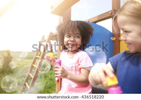 Blowing soap bubble with the best friend  - stock photo