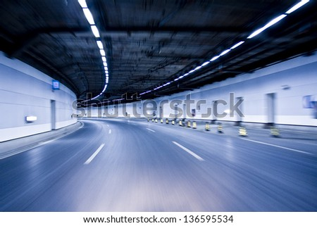 Blue Abstract blurred speed motion in urban highway road tunnel, moving toward the light - stock photo