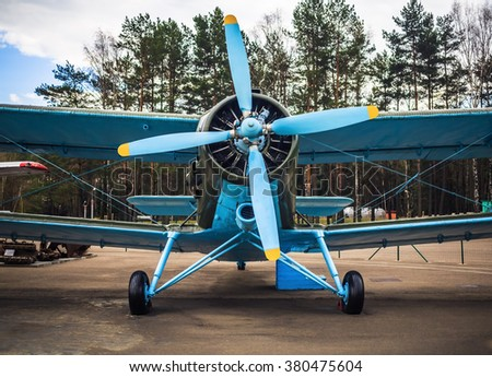 Blue airplane with propeller. Vintage biplane. Front view, with the side of the fuselage. Old retro plane close-up. - stock photo
