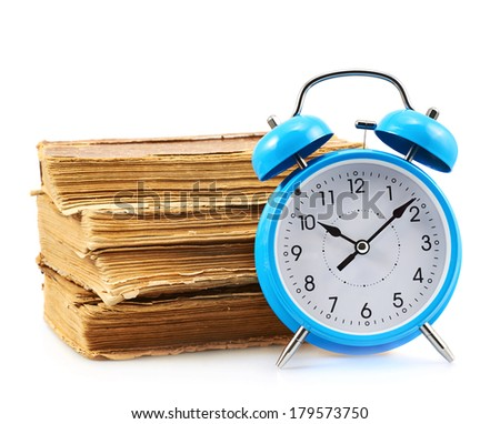 Blue alarm clock in front of the stack of the old books isolated on the white background - stock photo