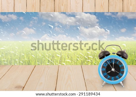 Blue alarm clock on table wood texture with rain drops on a window or water drops on grass blurred with green rice field and blue sky. - stock photo