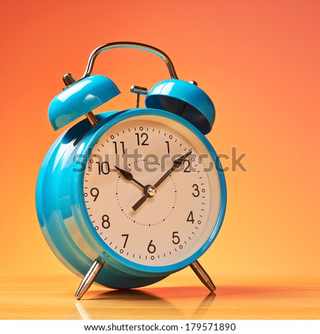 Blue alarm clock on the wooden surface against the orange background - stock photo