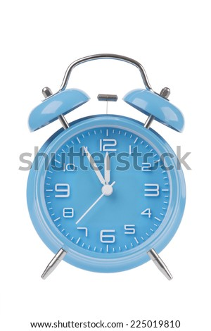 Blue alarm clock with the hands at 5 minutes till 12 illustrating time is running out isolated on a white background - stock photo