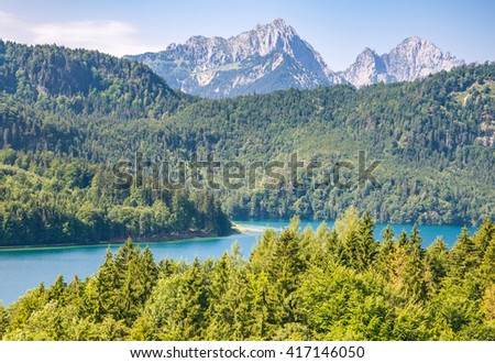Blue Alpsee Lake in the Green Forest and Beautiful Alps Mountains in the Morning Fog. Fussen, Bavaria, Germany