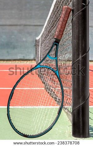 Blue and black tennis racket leaning on metal pole by the net. Front view. Net and court blurred background.