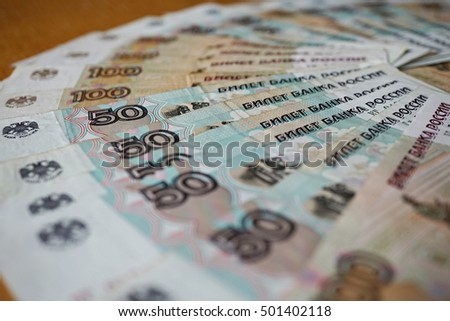 Blue and brown bank notes in the value of fifty and one hundred Russian Rubles forming the shape of circle