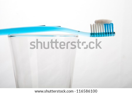 Blue and Clear tooth brush in glass Isolated on white background