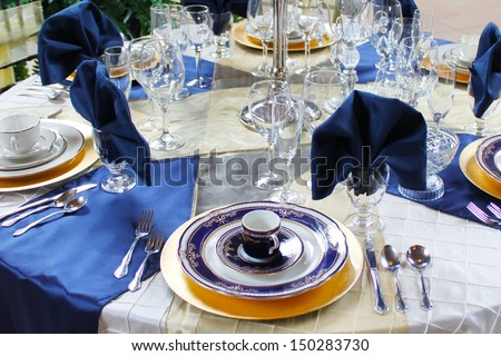 Blue and gold dishes set on a table - stock photo