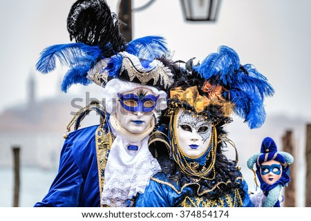 Blue and gold masked couple  with carnaval costumes, Venice, Italy. - stock photo