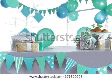 Blue and green colored birthday party table with sweets and decorations - stock photo