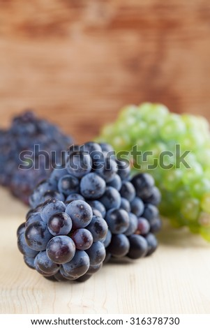 Blue and green grape clusters on wooden background. Shallow dof - stock photo
