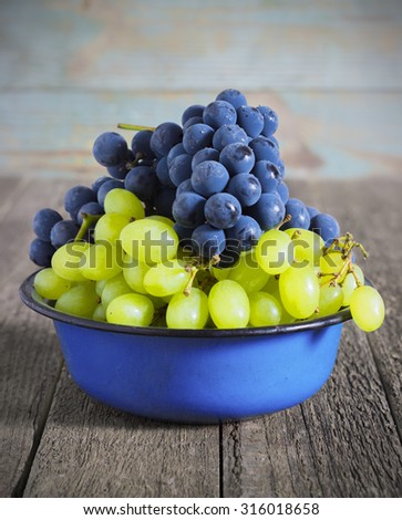 blue and green grapes in a metal bowl on a wooden background   - stock photo