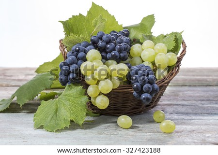 Blue and green grapes in a wicker basket on a wooden surface. Green grape leaves. Bunches of grapes. - stock photo