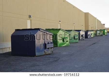Blue and green industrial garbage bins lined up outside along commercial building - stock photo