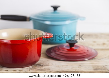 Blue and open red saucepans - stock photo