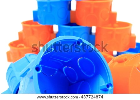 Blue and orange plastic electrical boxes on white background, components for use in electrical installations, accessories for engineering jobs