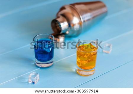 Blue and orange shots near metal sheker on wooden background. - stock photo