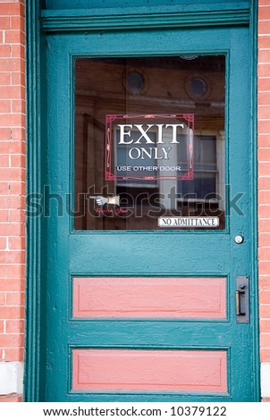 Blue and pink door with exit only sign - stock photo