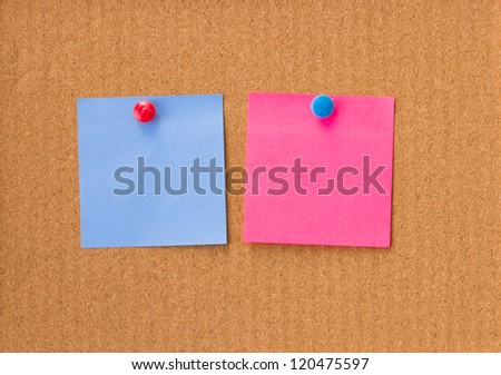 blue and pink empty notes on cork background