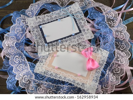 Blue and pink greeting cards with lace on wooden background - stock photo