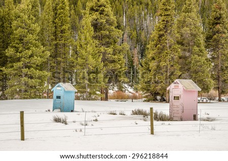 Blue and pink outhouses at a campground make it easy to tell where the boys and girls should go - stock photo