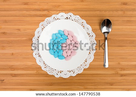 Blue and pink pills on a bone china saucer, arranged in a shape of yin and yang, served on a desk with a fancy napkin and a tea spoon - stock photo