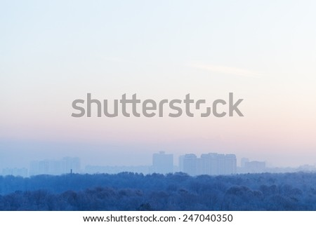 blue and pink sky over city in cold winter sunrise - stock photo