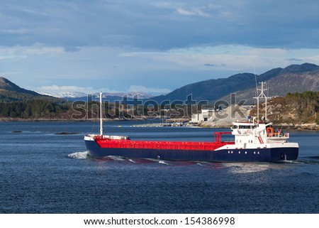 Blue and red general cargo ship sails on Norwegian fjord - stock photo
