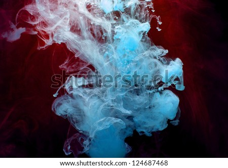 Blue and red Ink in water on a black background. - stock photo