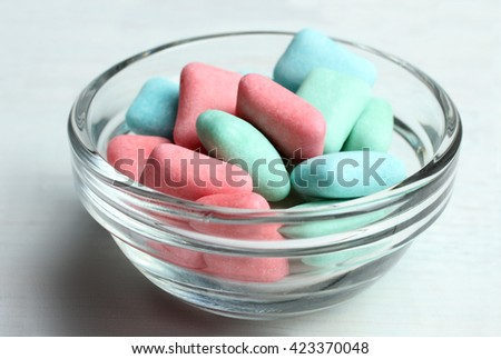 blue and red with green chewing gum in bowl on white wooden background