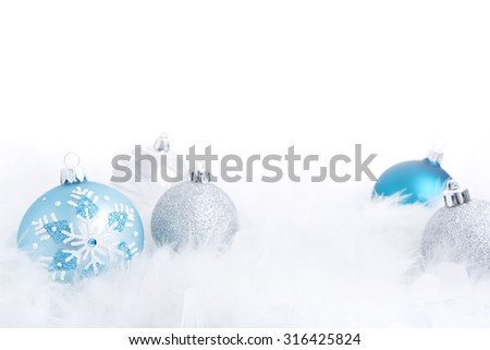 Blue and silver Christmas baubles on a soft feathery surface with a white background. - stock photo