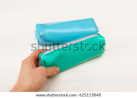 Blue and turquoise pencil case on white background