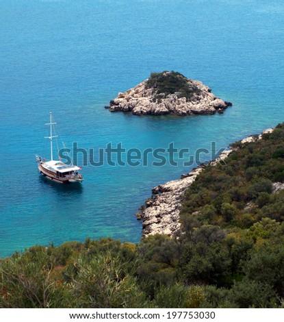 Blue and turquoise sea,  rocky beach with green vegetation, little island and  sailing, Turkey, kaputas beach - stock photo