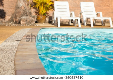 blue and vibrant swimming pool side in Thailand - stock photo