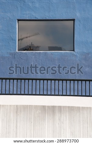 Blue and wall with window showing reflection  - stock photo