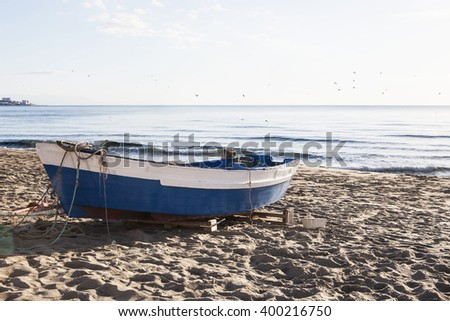 Blue and white boat on the sand at the beach