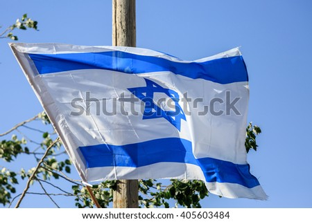 Blue and white flag of state Israel waving in the wind - stock photo