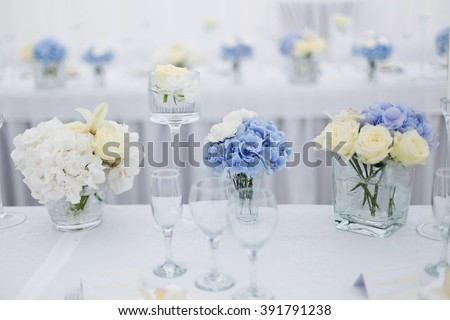 blue and white flowers decorate the table - stock photo
