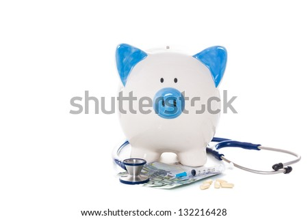 Blue and white piggy bank sitting on euro notes with stethoscope syringe and pills - stock photo