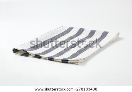 blue and white striped dishtowel on white background - stock photo