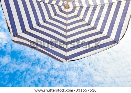 Blue and white sun protection beach umbrella and blue sky with clouds. Vacation resort, tropical paradise. Croatia Adriatic Sea - stock photo