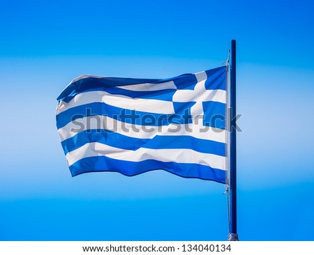 Blue and white the Greek flag in the wind against the blue sky - stock photo