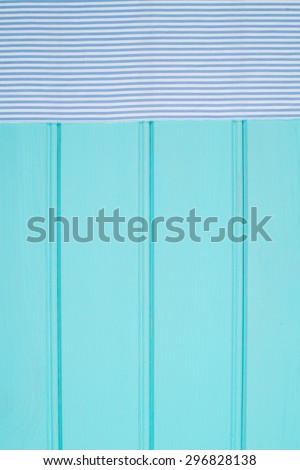 Blue and white towel over the surface of a wooden table. - stock photo