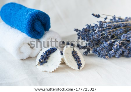 Blue and white towels, lavender bouquet and lavender soap on a linen napkin