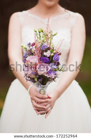 blue and white wedding bouquet in the hands of the bride - stock photo