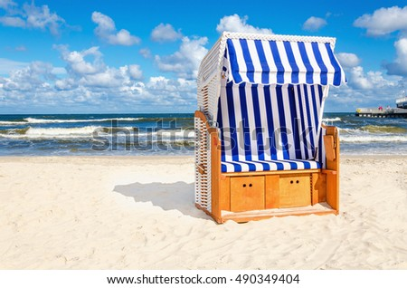 Blue and white wicker chair on sandy beach