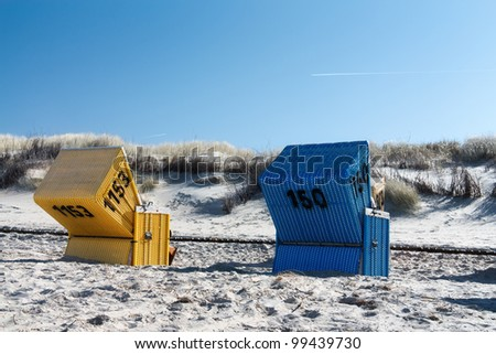 Blue and yellow beach chair on Langeoog with blue sky and a condensation trail. - stock photo